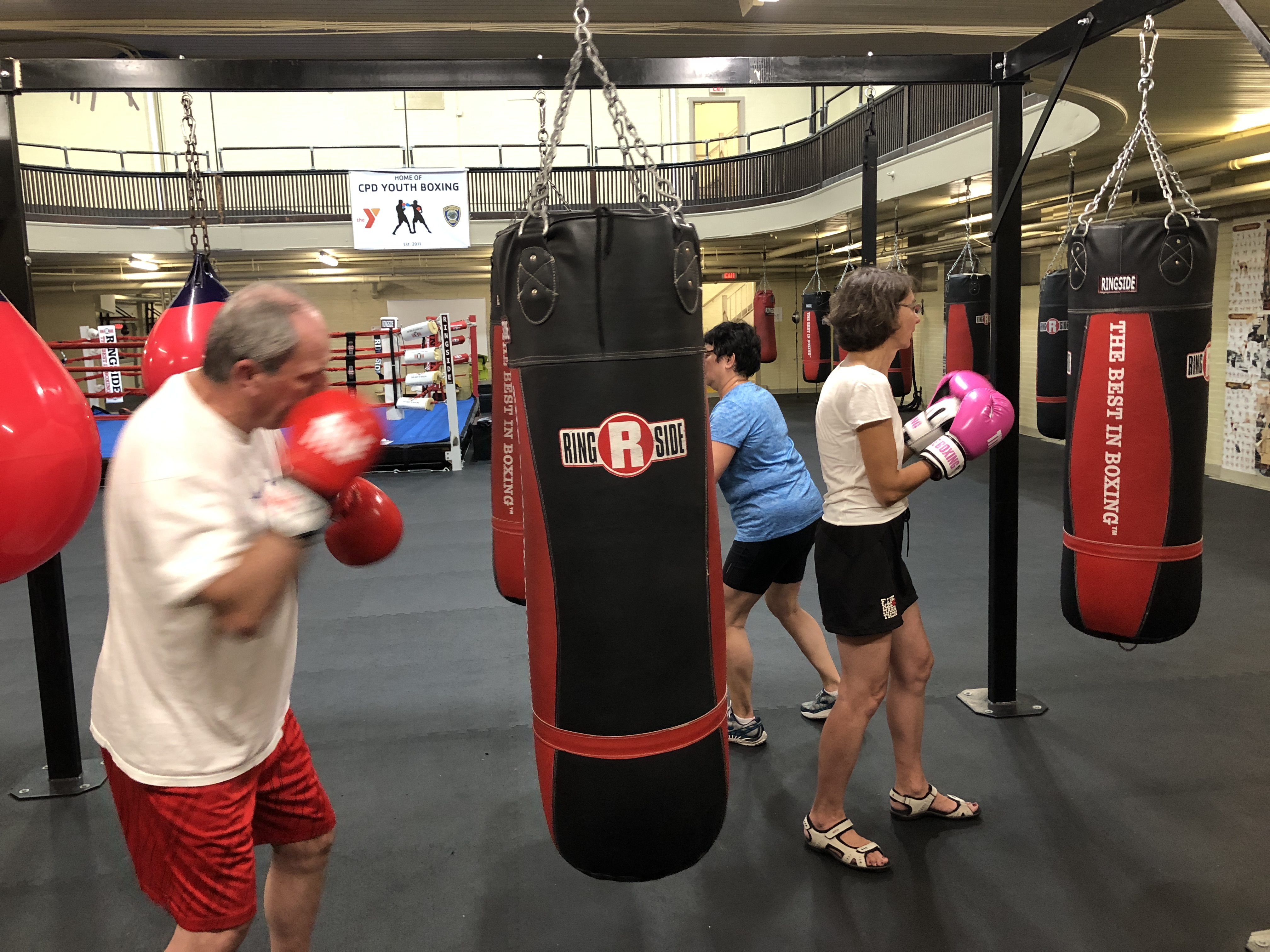 Photo: Three Rock Steady Boxing students punching individual bags.