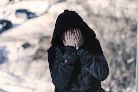 Photo: figure of human in dark clothing and hood with hands covering face in apparent shame or fear