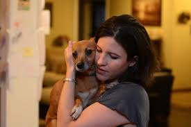 Closeup photo of woman comforting small dog, holding them close to her face.