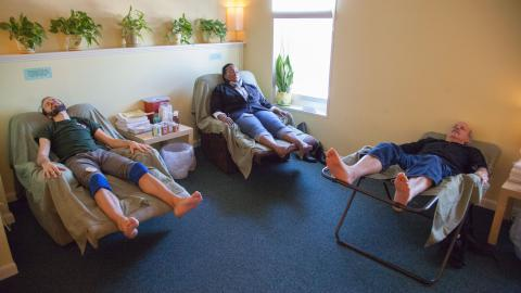 Photo: Three adults in reclining chairs with acupuncture needles inserted.