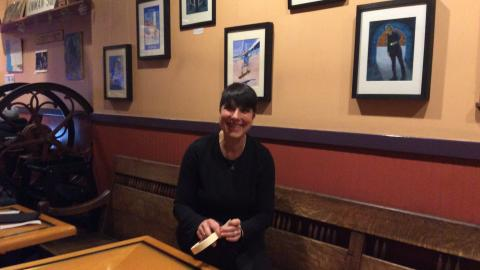 Photo: Jules Kobek sitting at table in coffeehouse, in front of hanging Proletariat tArot images on wall.