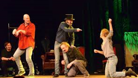 men and women performing active improv on a stage