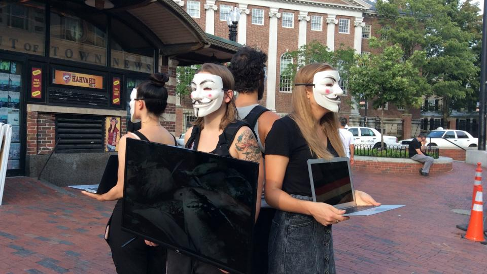 Four AV Cube participants  standing back-to-back, dressed in black, wearing anonymous masks, holding TV screens in Harvard Square.