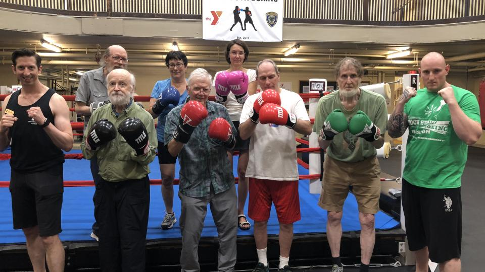 Group Photo: Seven RSB students, in a line in front of boxing ring, flanked by Al and Matthew (RSB coaches)