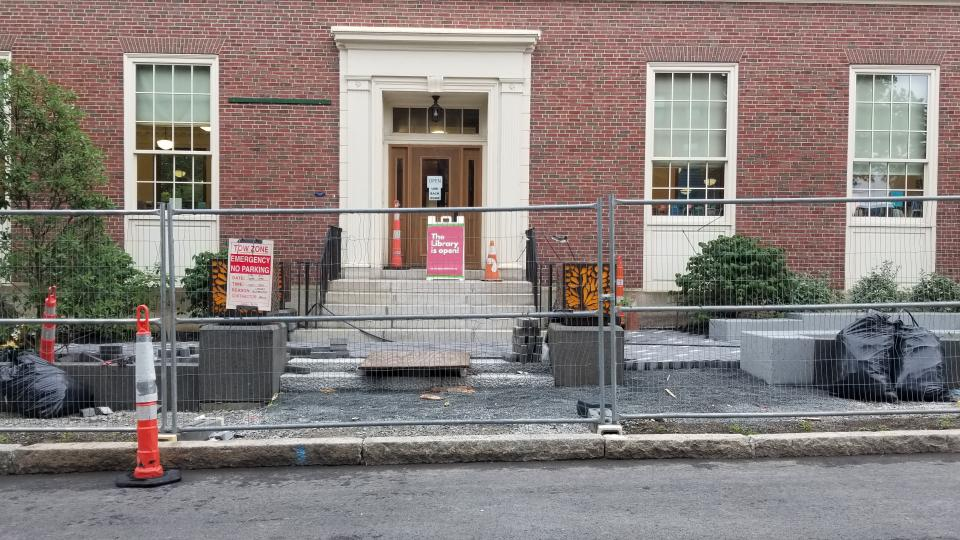 Photo, brick library facade with construction in progress behind cahin link fence